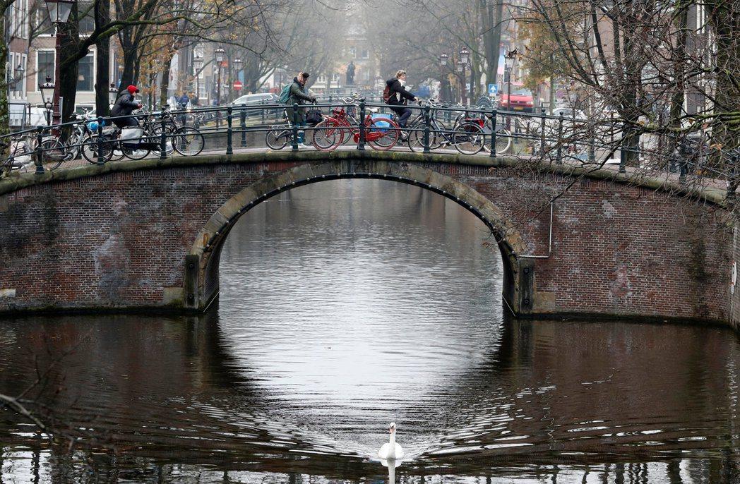 今年「好國家指數」榜首是荷蘭,圖為荷蘭阿姆斯特丹民眾騎車經過市中心橋梁。路透