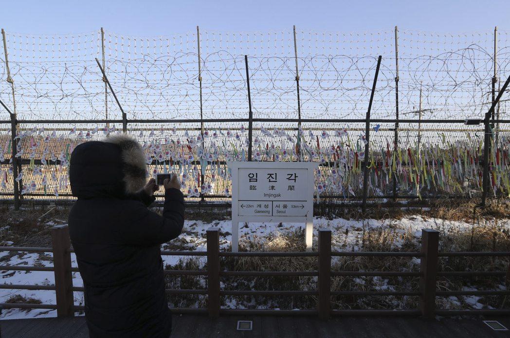 圖說:一名遊客19日在南韓坡州臨津閣拍照,告示牌標明當地與南韓首都首爾與北韓開城...