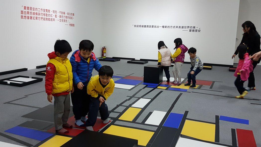 老師帶領學生在「跳舞方塊」區域遊戲,學生興奮地在線條上或方格上行走,與生活中的色...
