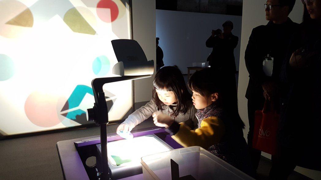 「影子遊戲」工作坊讓學童隨機拿起網布等各式物品,透過螢幕投射出物品的形狀及色澤,...