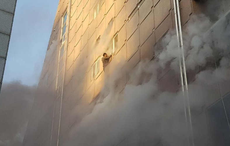 一名男子攀在失火的建築窗外,等待救援。路透