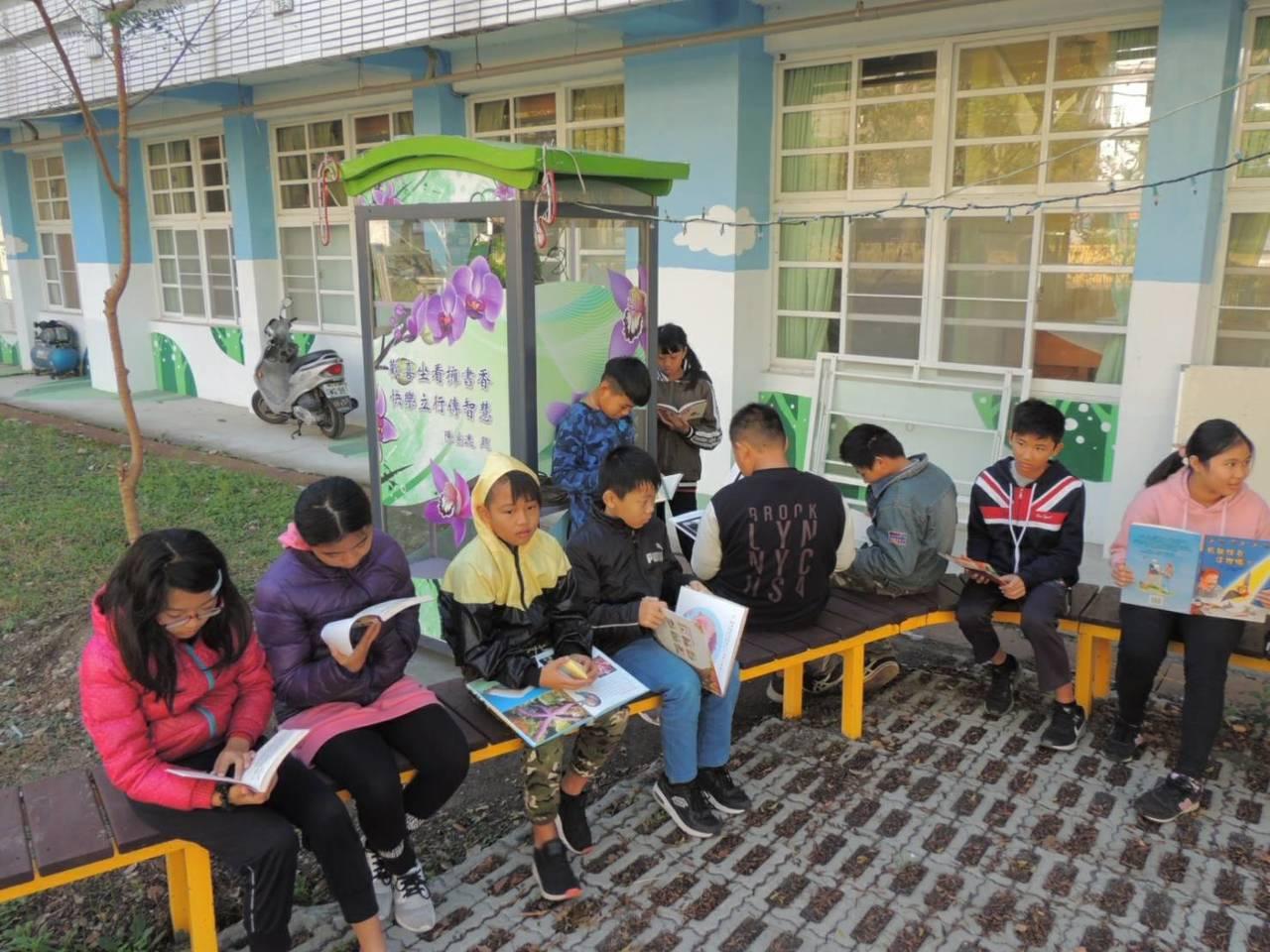 學童在電話亭前閱讀,假日還會有遊客進入校園看書。 記者徐白櫻/攝影
