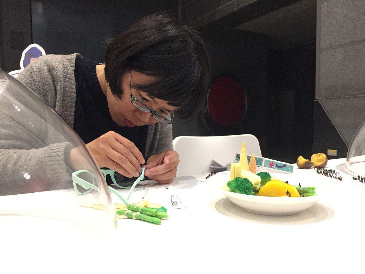 國內知名雕塑家林玉婷仔細小心地將1:200的小人偶貼在作品上。 記者陳珮琦/翻攝
