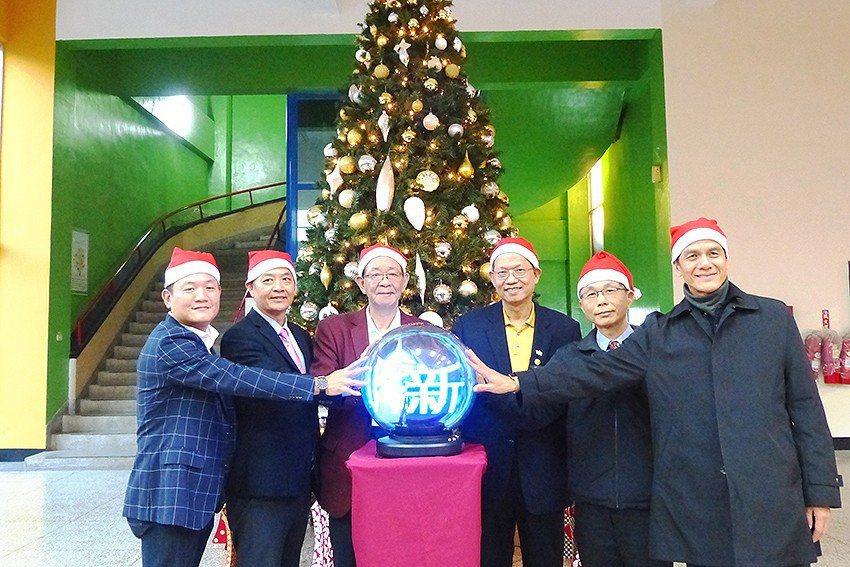 聖誕節前,明新科大校友聯瑩工藝總經理張珈源(左)捐贈聖誕樹,特別舉辦點燈祈福活動...