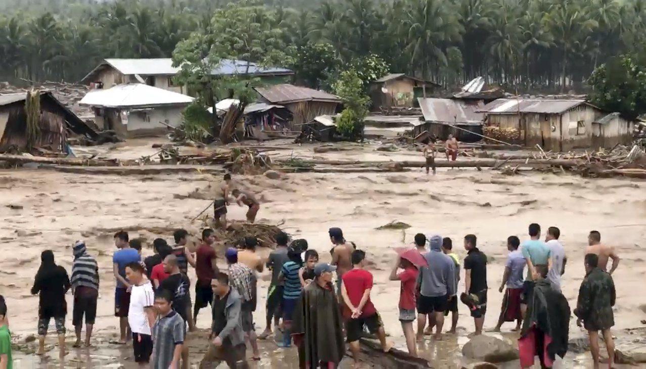 菲律賓村民協力渡過滾滾洪流。美聯社