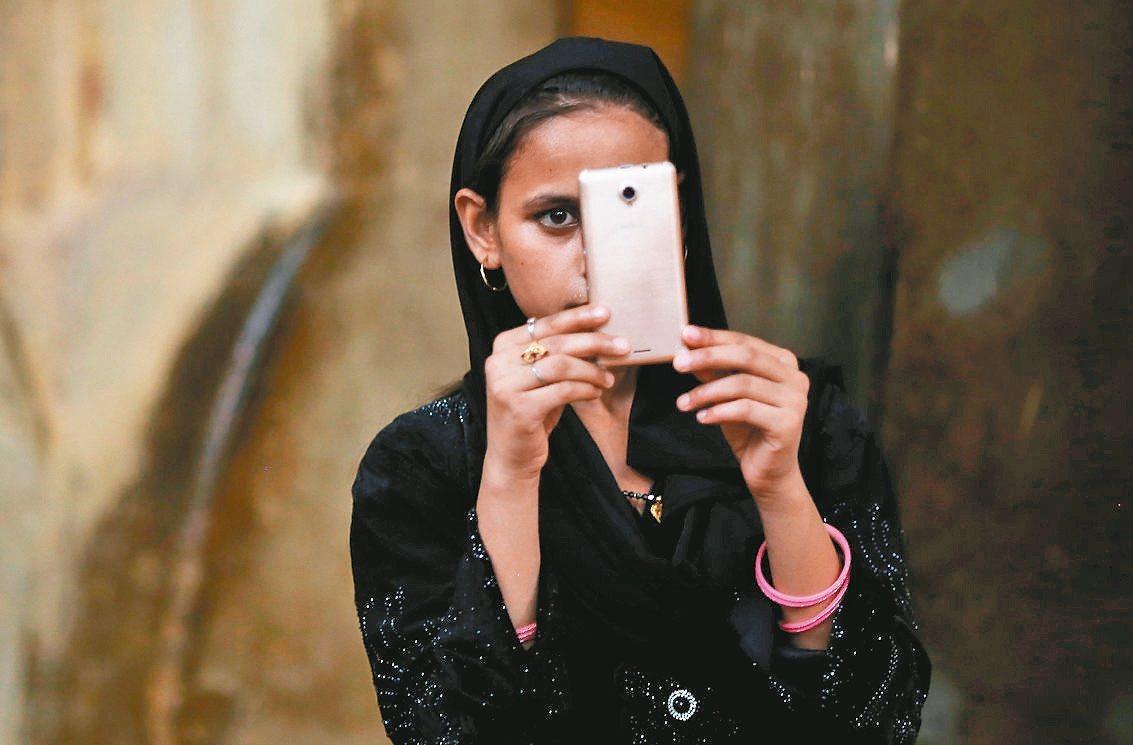 印度女孩用手機拍照。 路透
