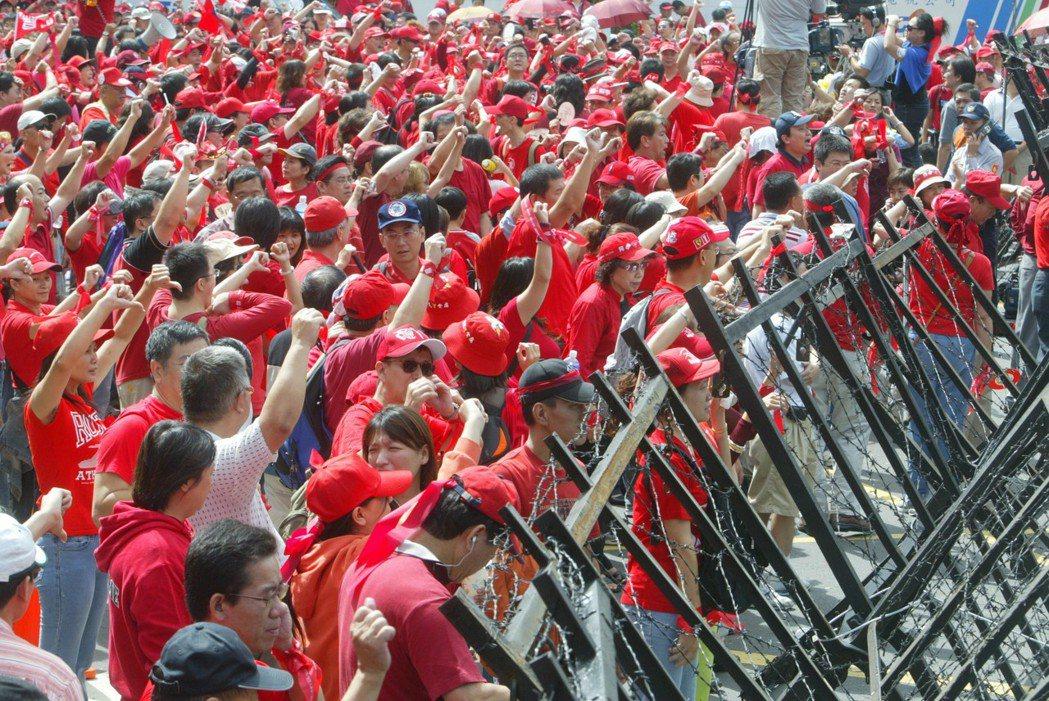 反貪腐倒扁總部2006年在國慶日發起「天下圍攻」,倒扁紅衫軍隔著拒馬與警方對峙。...