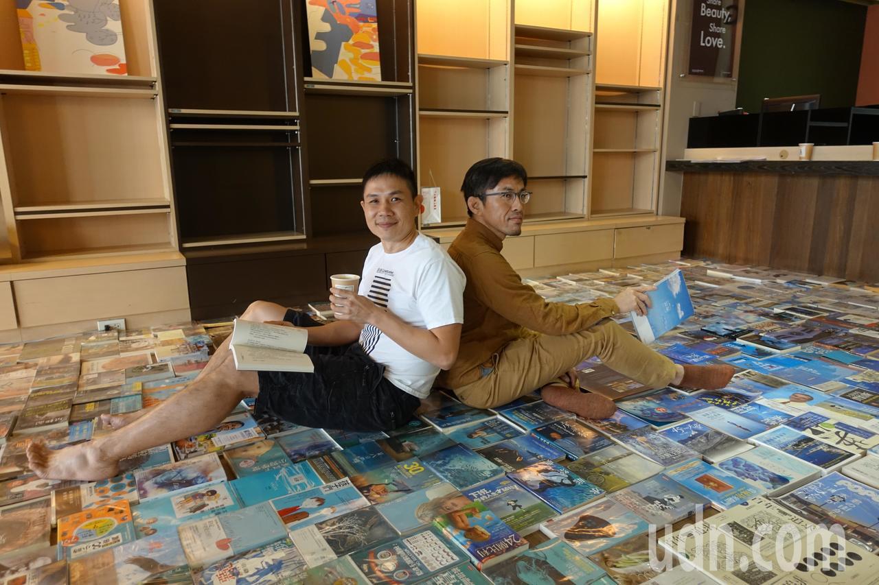 BOOKING老闆李昆霖(左)與藝術家Larry,將近2800本的書本攤開擺在地...