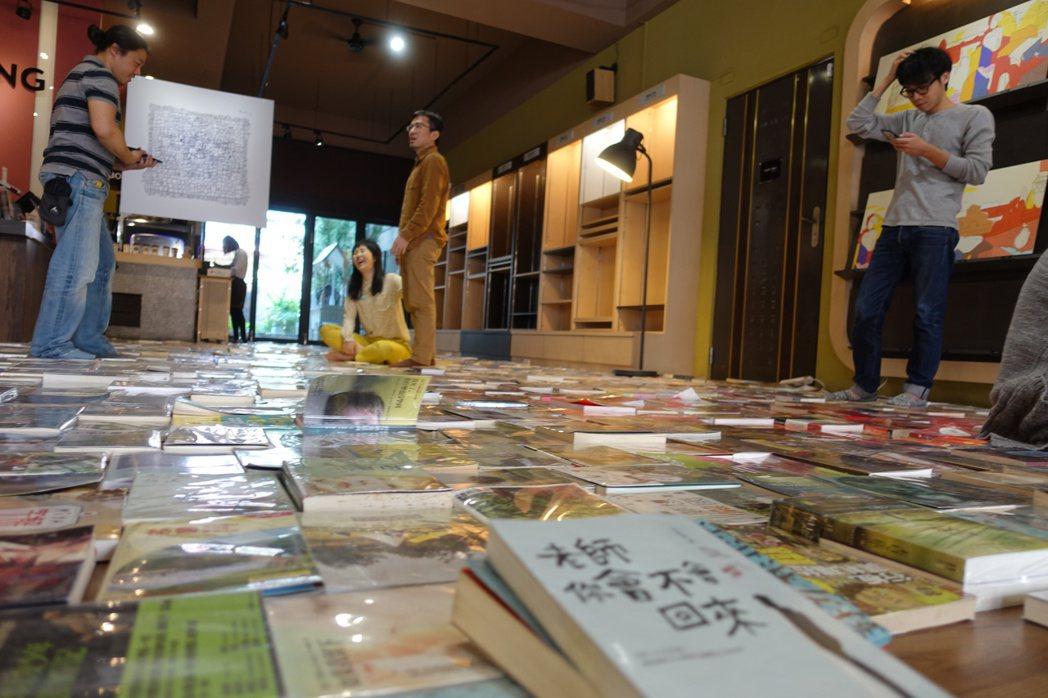 近2800本的書本攤開擺在地上,透過顏色分類,看見不一樣的書店風景。記者劉星君/...