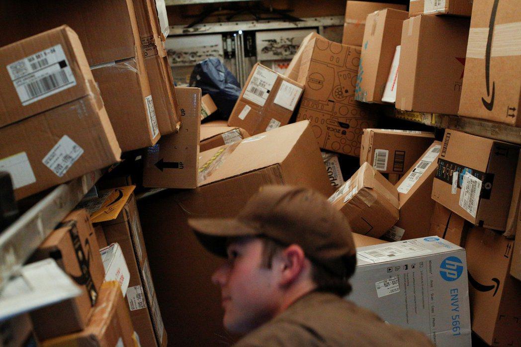 美國西雅圖的一名優比速快遞員在滿載包裹的送貨車內找尋一個包裹。路透