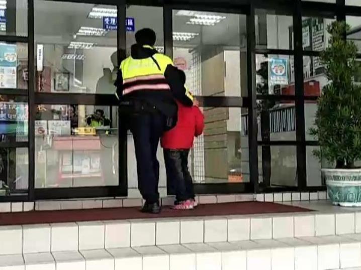 員警帶著邊吃披薩的小男童走進分駐所,打電話找媽媽。 記者林昭彰/翻攝