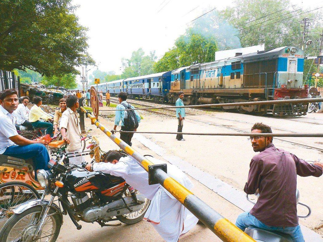 印度鄉鎮間的火車平交道一景。 謝旺霖