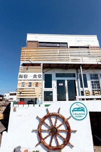 坐落在海灘上的「海宿食堂Good Morning材木座」,白色的外牆映襯著藍天與...