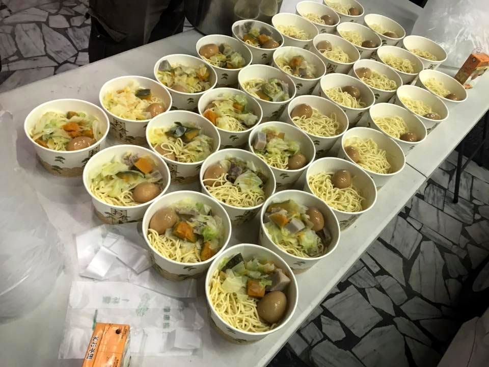 張泓德等人準備一碗碗熱騰騰的麵食,發送給街友享用。圖/張泓德提供