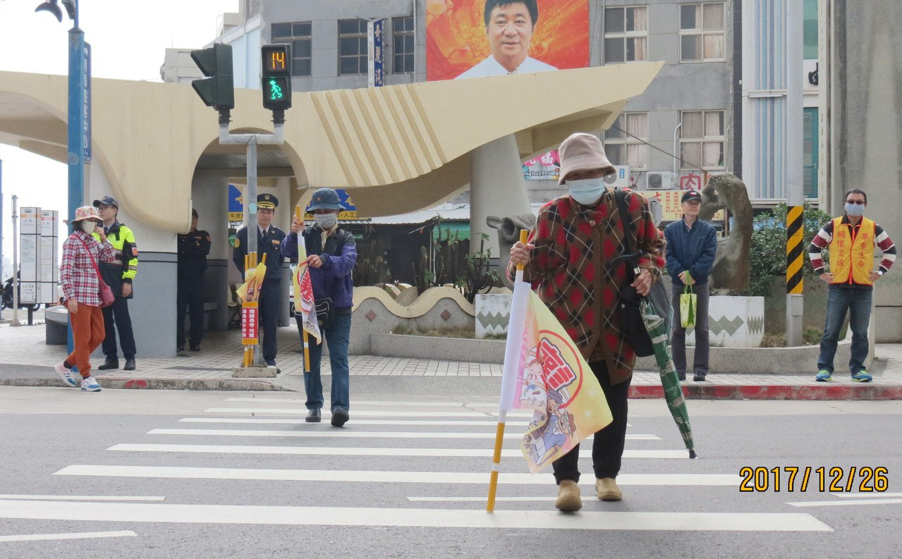 澎湖警方今在馬公市試辦行人「優先旗」,希望讓年長者過馬路更有保障。圖/澎湖縣警局...