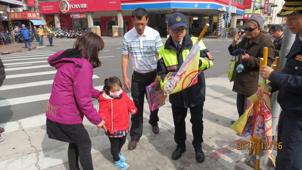澎湖警方仿日本做法試辦穿越人行道「優先旗」,今天由員警告訴往來的老少使用方式。圖...