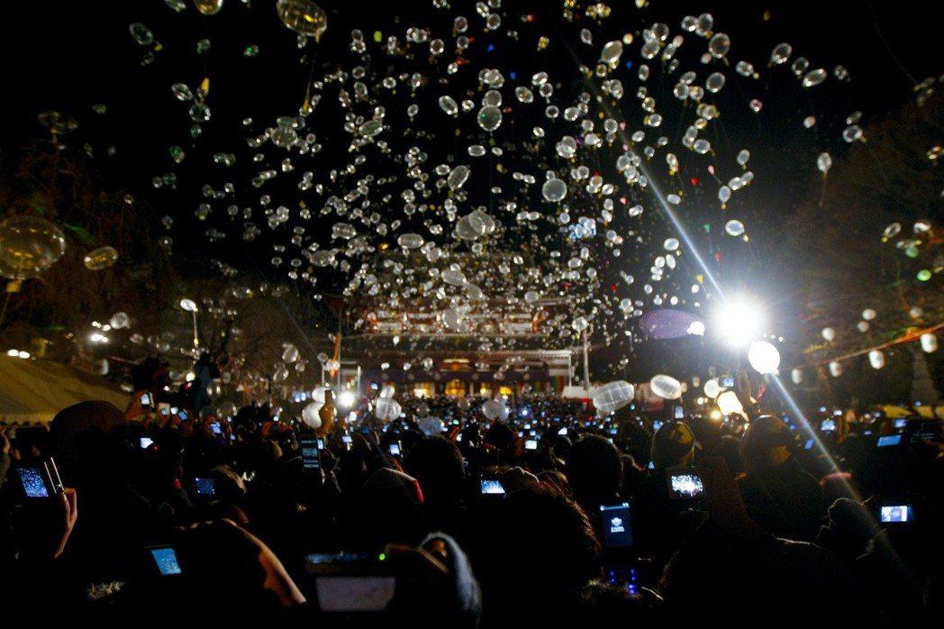 日本東京增上寺舉辦跨年夜活動,讓民眾將新年新希望裝在氣球裡升空。 歐新社
