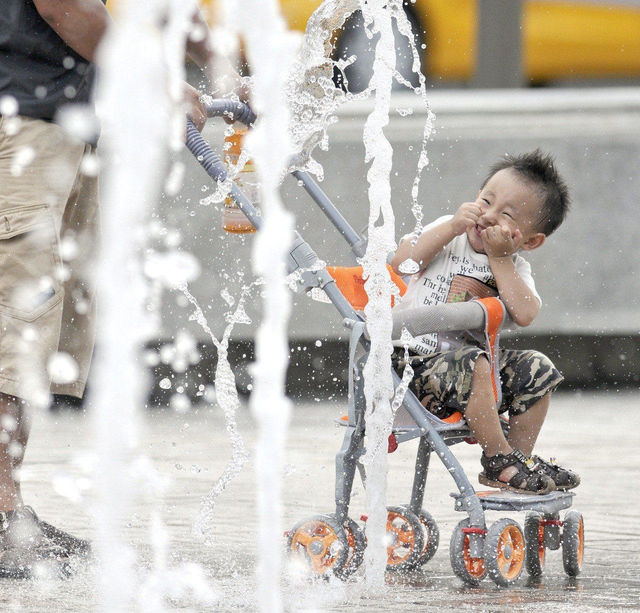 一個爸爸推著坐在嬰兒車上的小朋友穿梭在噴起的水柱間。聯合報系資料照/林澔一攝影
