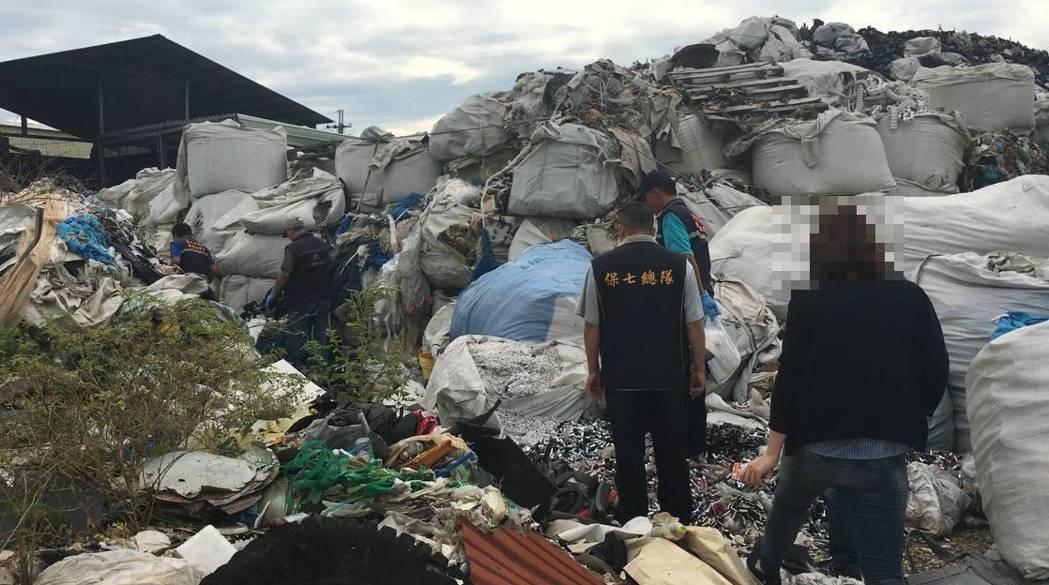 台中檢警查獲一座空地被放大量廢棄物,員警進入垃圾山搜證。圖/警方提供