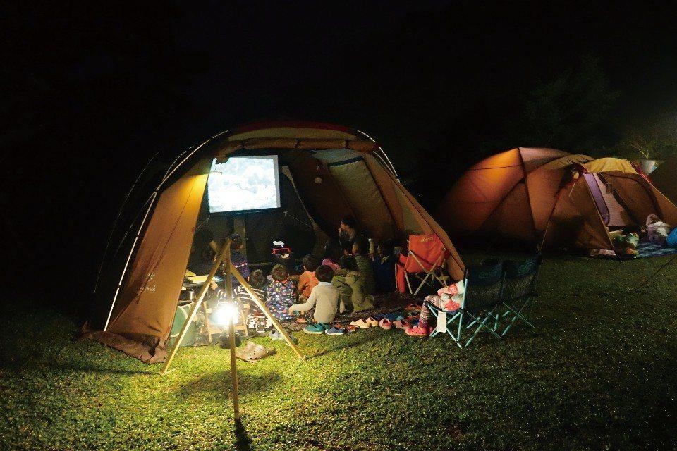 一家人窩在帳篷中,享受溫馨的電影時光。(圖片來源/《劉太太和你露營趣》)