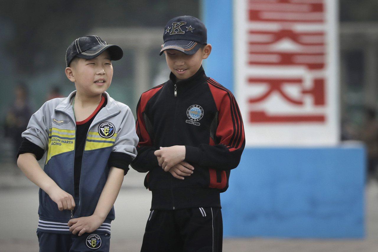 戴著棒球帽的兩名北韓兒童在平壤街頭邊走邊聊天。美聯社