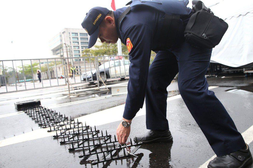 為避免車輛衝撞群眾,警方在重點路段備妥車輛攔阻器,車輛駛過會爆胎。 記者林俊良/...