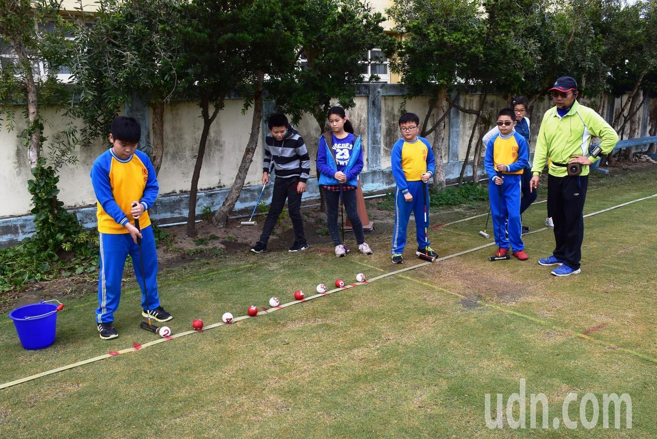 後寮國小總務主任傅禮聰(右1)指導學生專注打槌球的情形。記者何烱榮/攝影