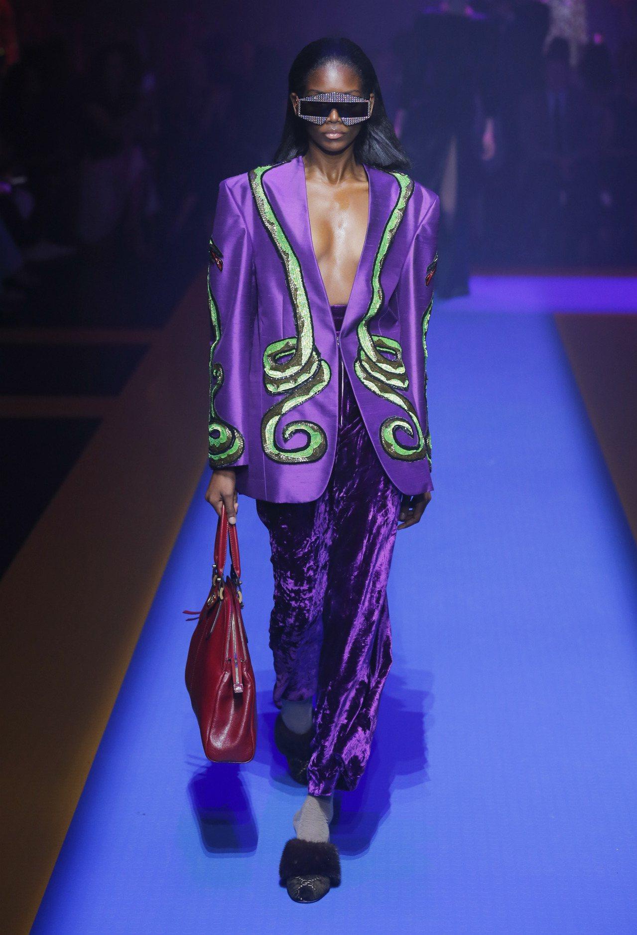 華麗搖滾風格造型運用深紫色西裝搭天鵝絨長褲穿出慵姿態。圖/Gucci提供