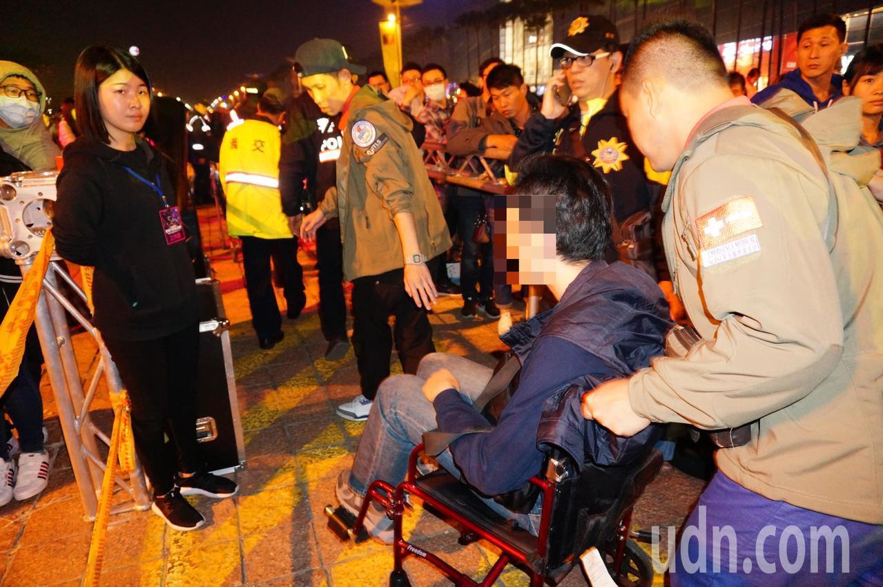 晚間9時半朱姓男子(右二)身體不適,由醫護人員推至會場旁。記者林伯驊/攝影