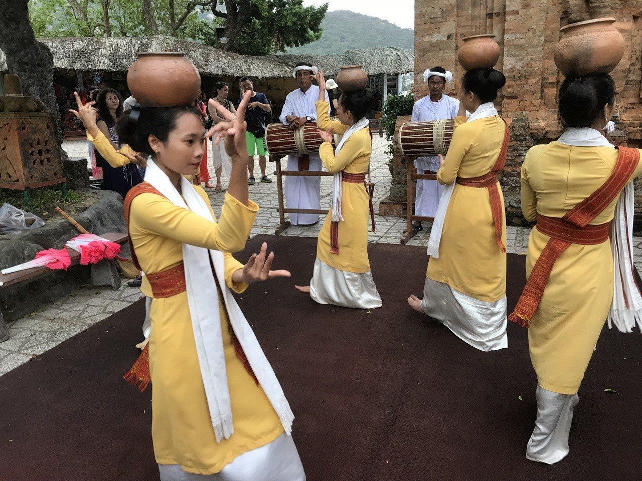 遊客在駐足占婆塔的同時,一旁的熱情舞者還會為大家跳一支南洋熱舞。 記者黃日暉/...