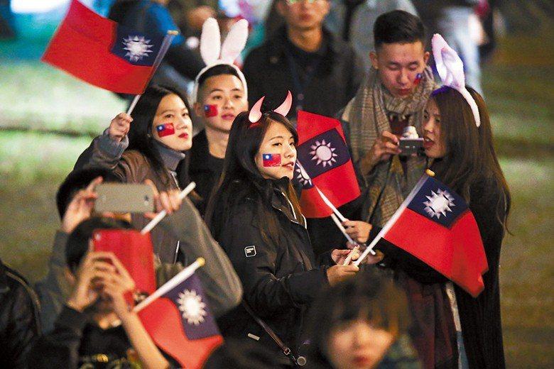 民眾參與元旦升旗典禮,開心與國旗合影留念。 圖/聯合報系資料照