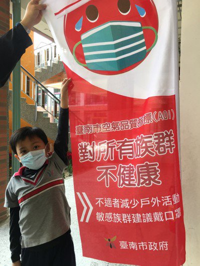 台南市空氣品質不佳,學校掛出空汙「紅旗」並提醒學生戴口罩保護。 記者吳淑玲/攝影