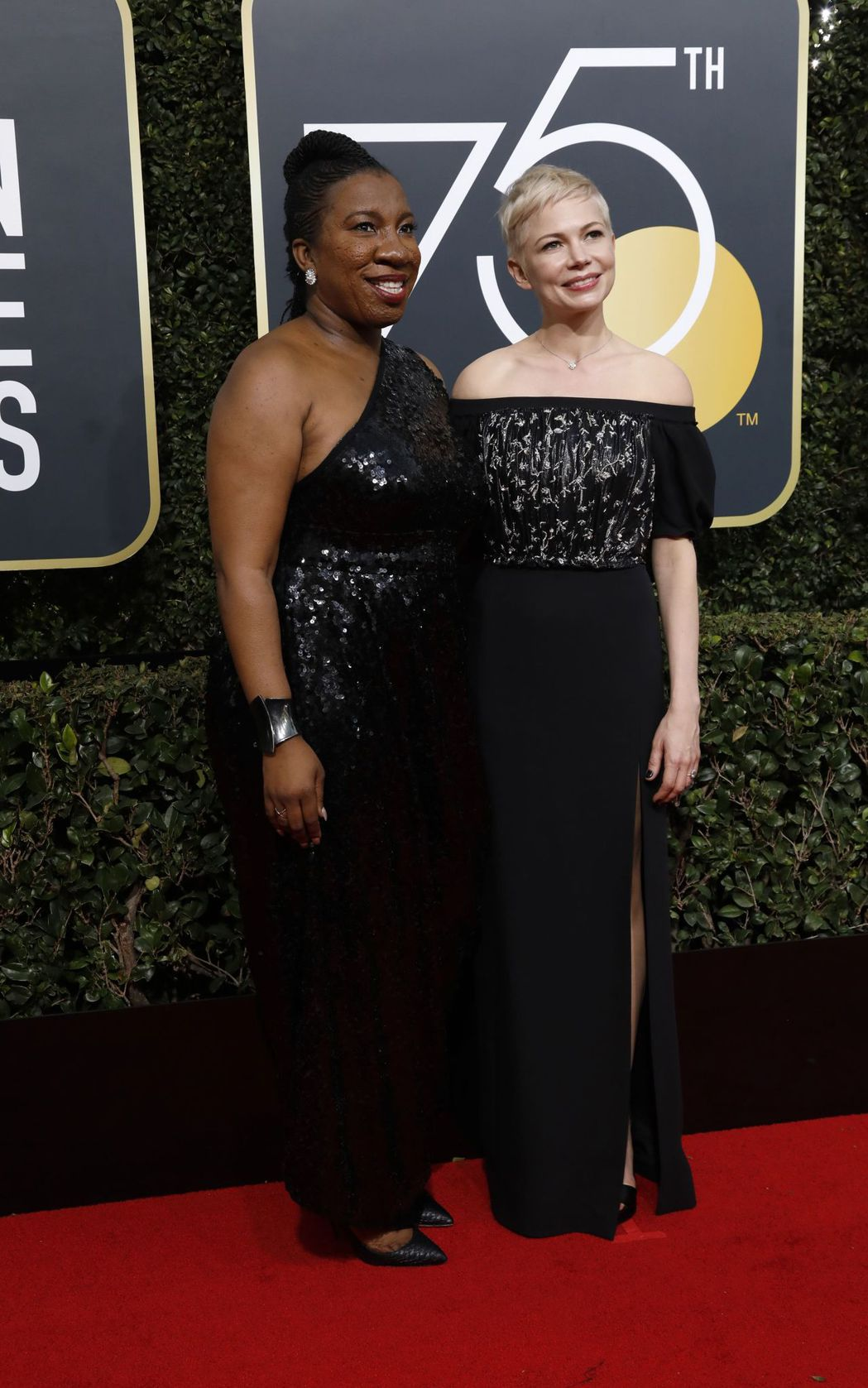 金球獎頒獎典禮紅毯上,美國女星蜜雪兒威廉絲(右)穿著一襲露肩花雕黑禮服,另一側則...