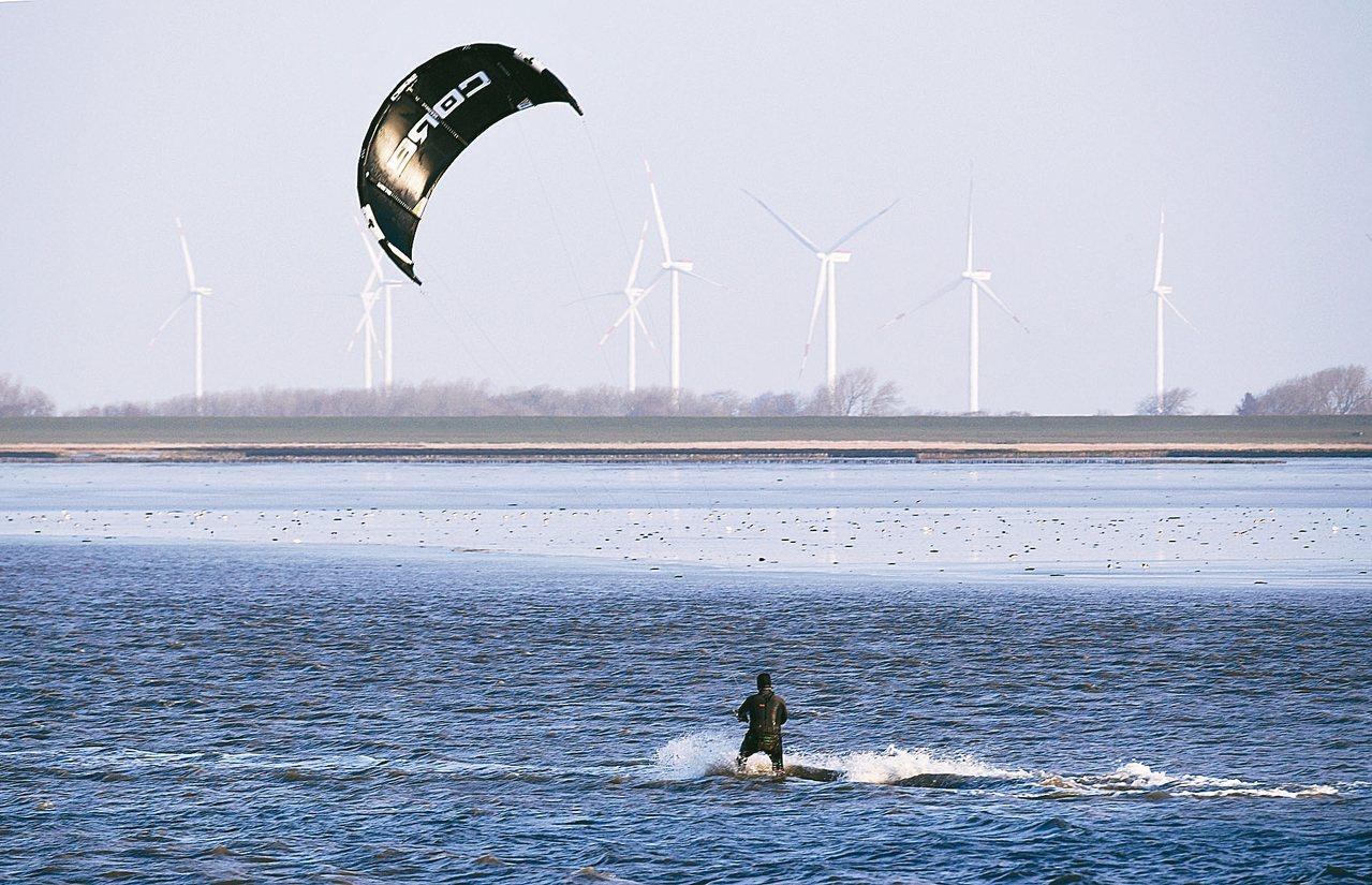 德國在今年元旦創下用電全來自再生能源紀錄,圖為一名男子三日在德國達格比爾沿岸玩風...