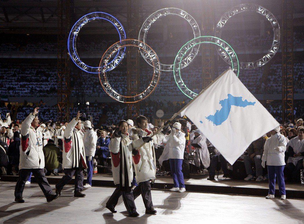 南韓選手李寶拉與北韓運動員韓正英在2006年杜林冬奧共同掌旗。 美聯社╱資料照片