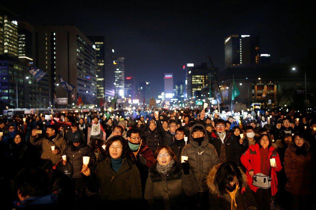 在要求朴槿惠下台的示威活動中,韓江首次走入人群,和成千上萬的民眾一起點燃微弱的燭光。 圖/路透社