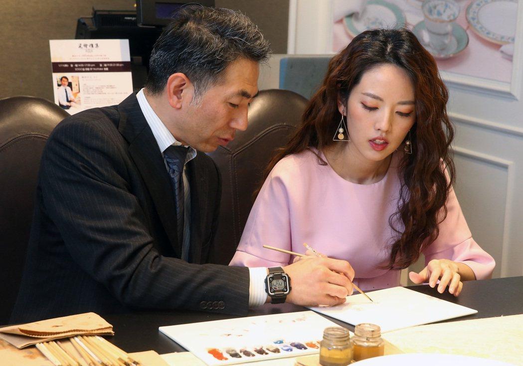 藝人阿諾(右)應邀出席瓷器品牌活動,並現場跟日本手繪大師岡田正己(左)學畫櫻花。...