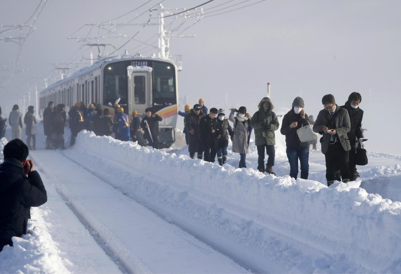 日本乘客12日早上離開被雪困住的JR信越線電車。 美聯社