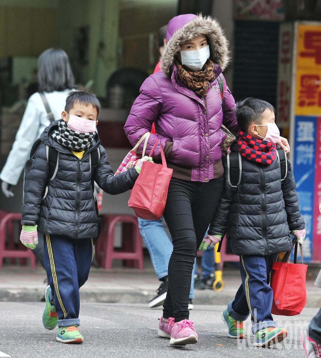 家長在寒風中穿著冬衣帶著孩子上學。記者鄭清元/攝影