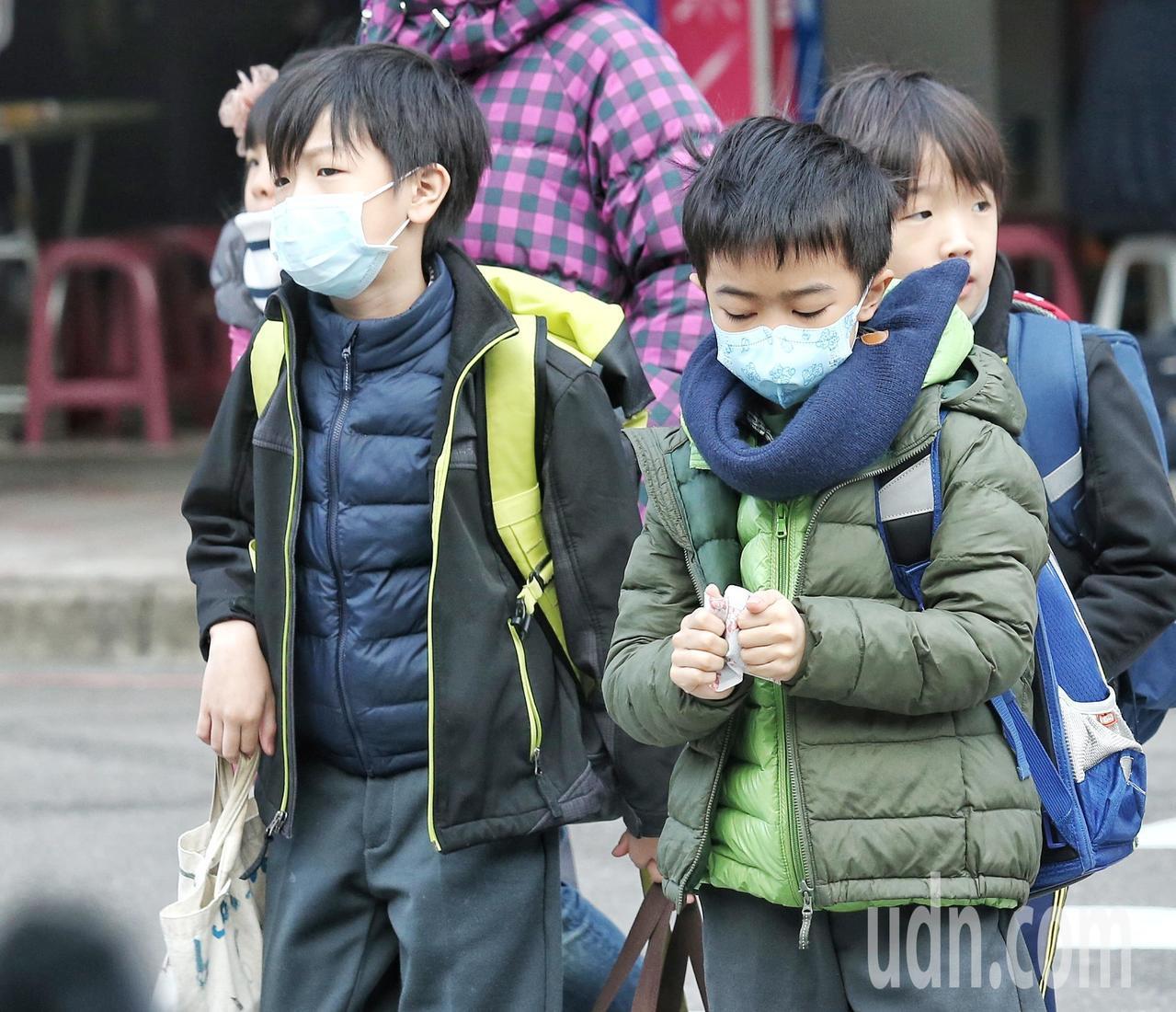 孩子身穿冬衣搓著暖暖包上學。記者鄭清元/攝影