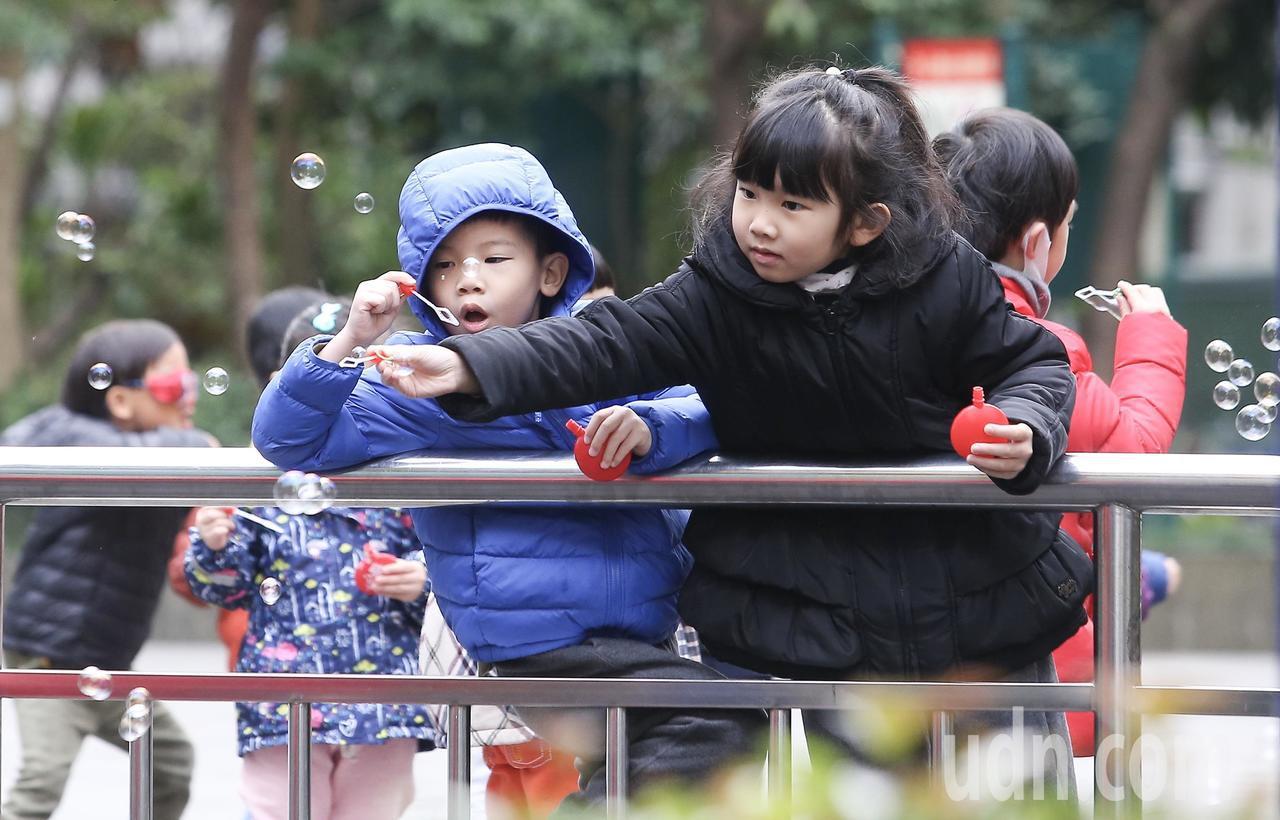 寒流持續發威,許多小朋友穿著禦寒衣物仍在公園玩得很開心。記者余承翰/攝影