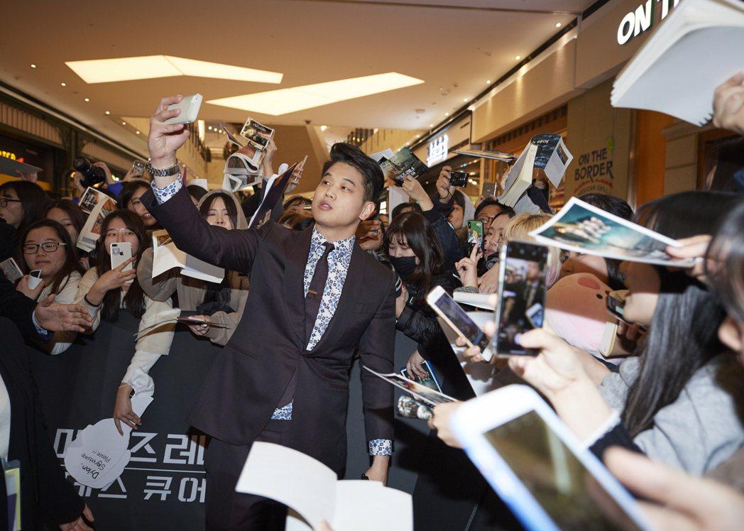 李基弘在「移動迷宮:死亡解藥」首爾首映會上與粉絲大方自拍。圖/福斯提供