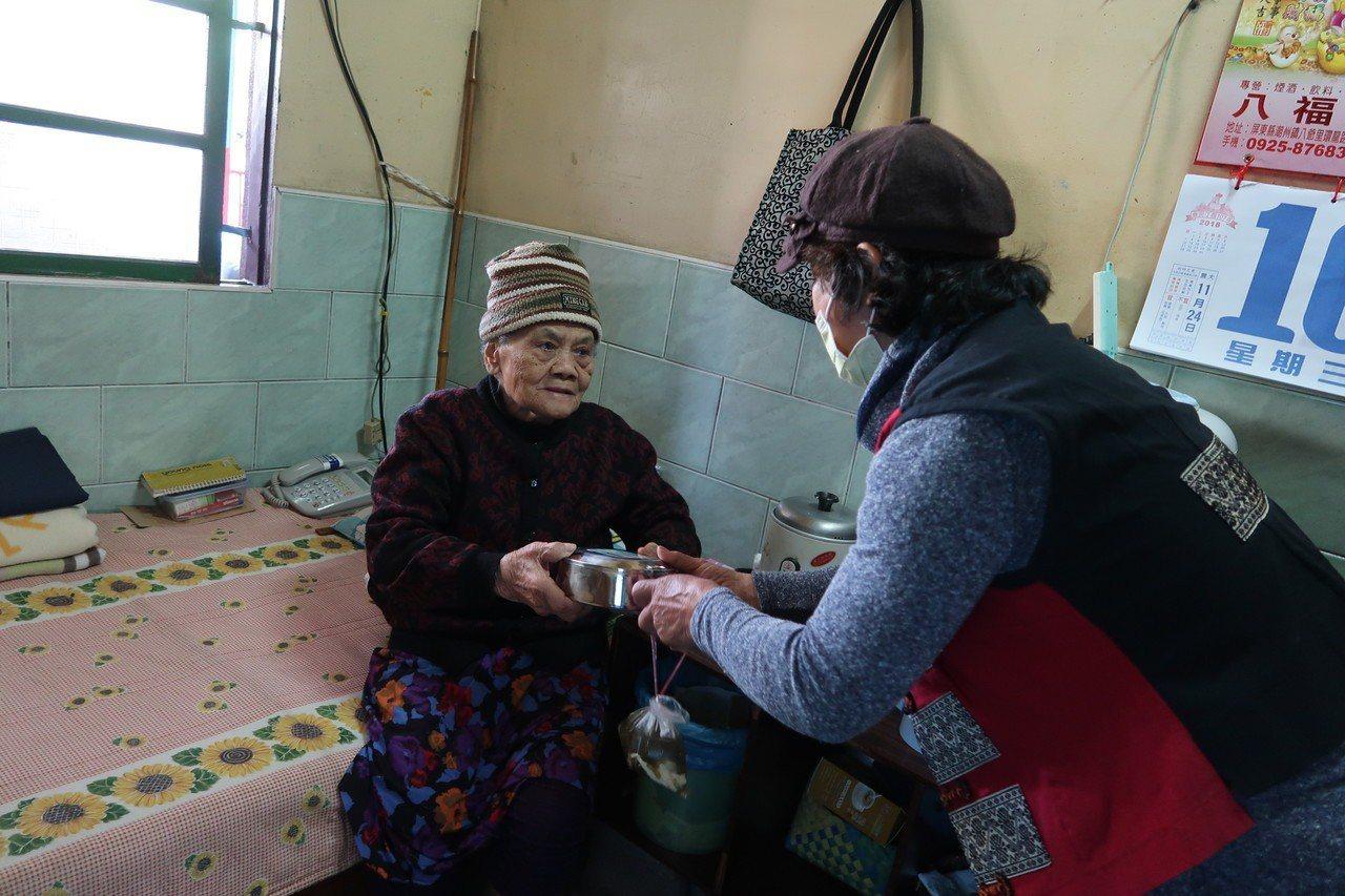 部落健康廚房的志工為老人送上熱騰騰的便當。 記者翁禎霞/攝影