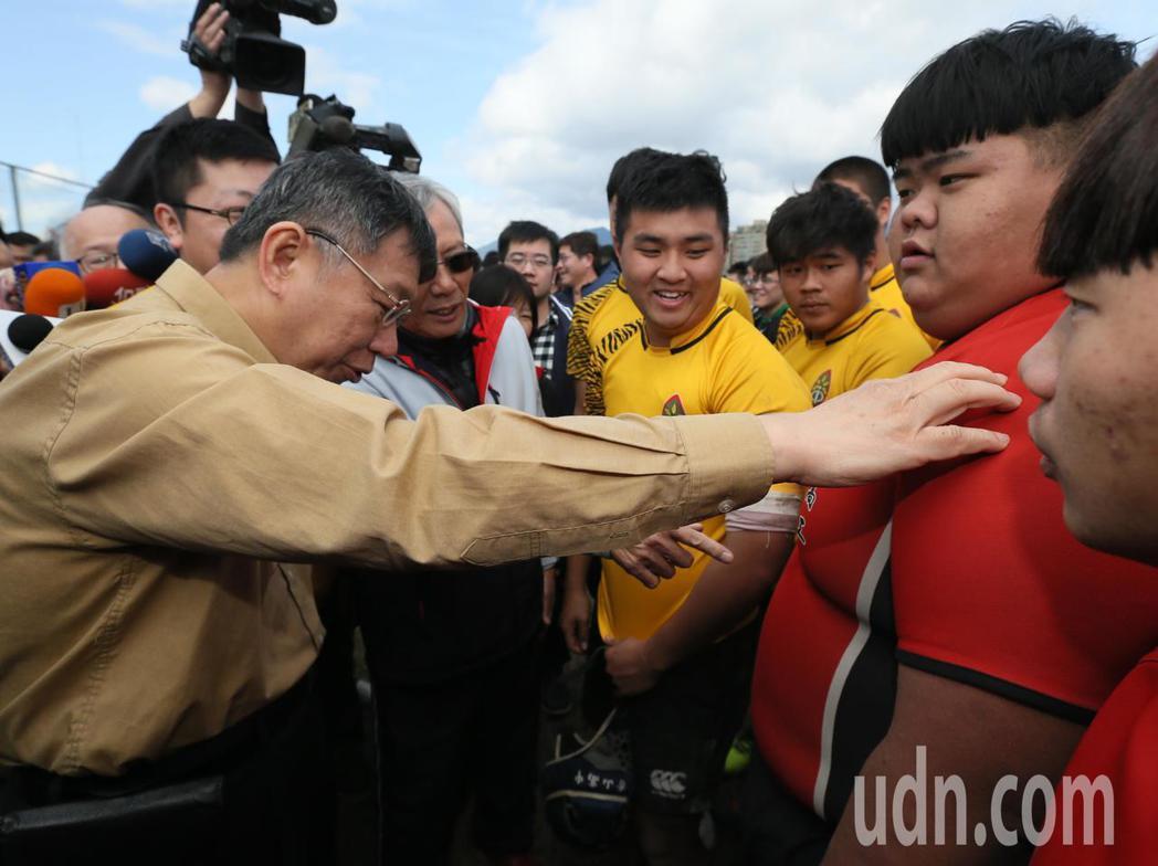 首屆市長盃橄欖球賽上午在百齡球場舉行,台北市長柯文哲(左)開球前與球員們握手打氣...