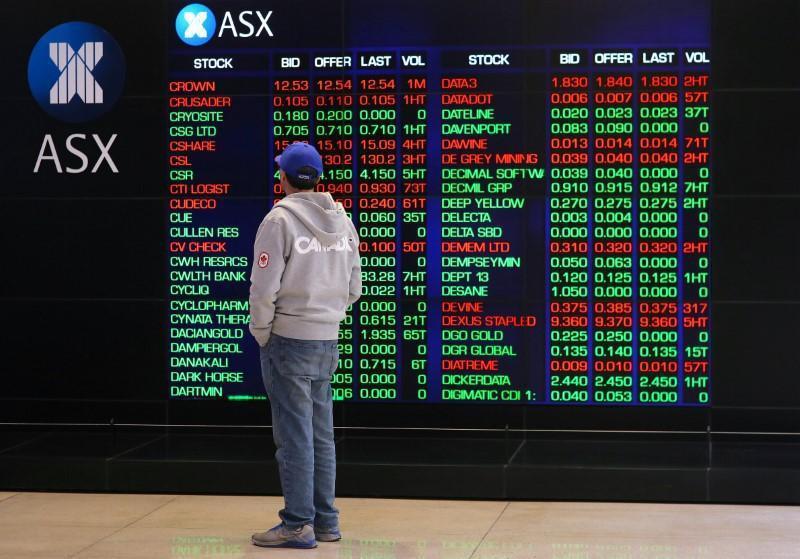 投資人站在顯示螢幕前觀看澳洲證交所股票行情波動的檔案照。路透