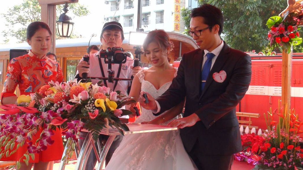 嘉義市集團結婚有29對新人參加,新人搭檜木小火車進場,留下難忘的婚禮回憶。記者王...