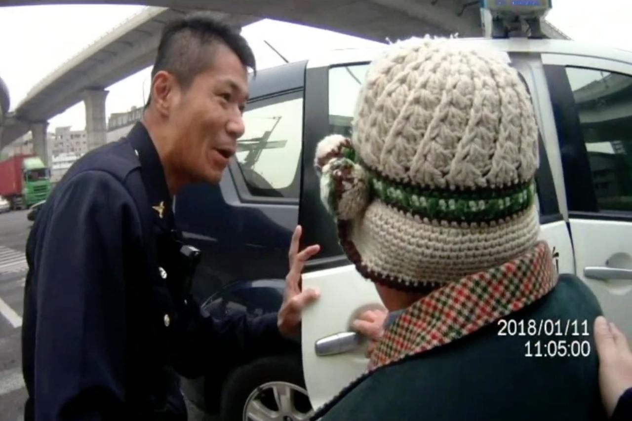 所長陳宗靖(左)將阿嬤的三輪車先移置到馬路旁邊,派出所的巡邏車來了,扶阿嬤坐上巡...