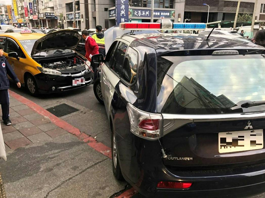 警車到場救援,讓計程車順利發動。記者蕭雅娟/翻攝