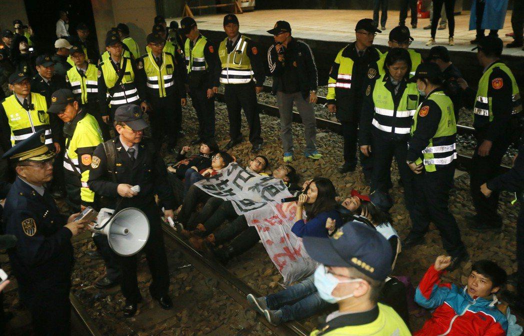 抗議勞基法修惡,勞團在北車月台臥軌抗議,鐵路警察派出大批警力進行排除。 圖/聯合...