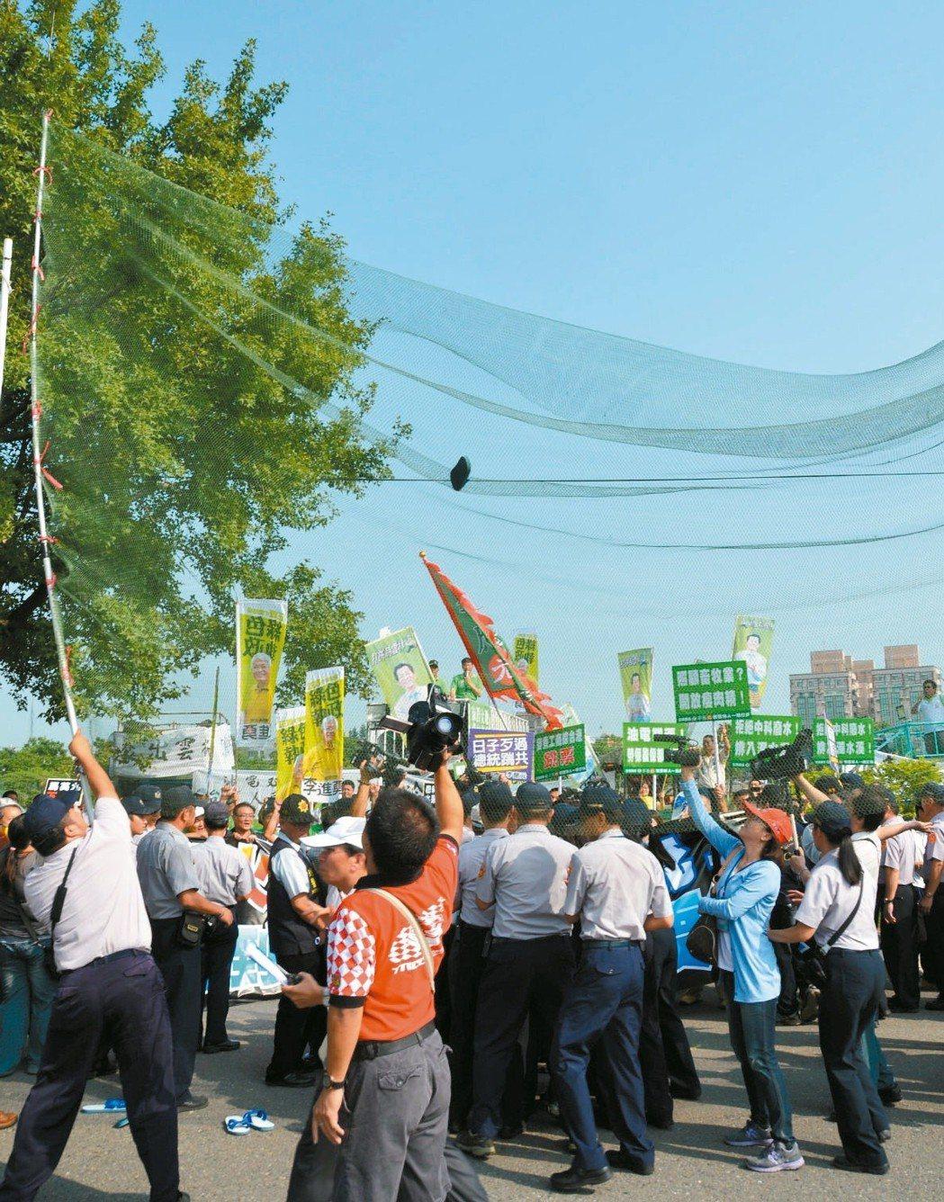 前總統馬英九曾被綠營人士嗆聲,有民眾丟鞋抗議(網中),被警方準備的高網攔截。 圖...
